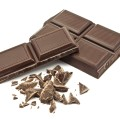 chocolate bar and broken up chocolate pieces on white background